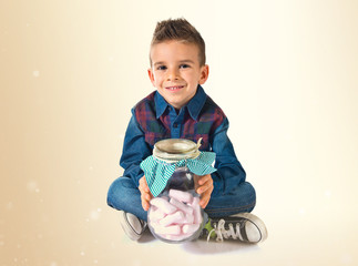 Kid holding a glass jar with sweets inside