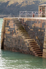 Harbour wall steps down to sea, Mullion, Cornwall, England