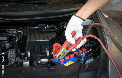 Poster automotive technician charging vehicle battery