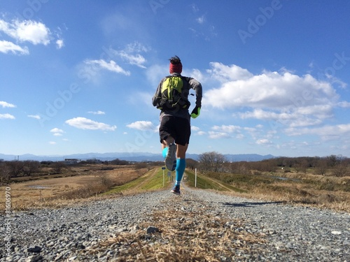 Male runner on long country trail