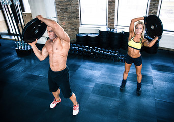 Muscular man and woman workout at gym