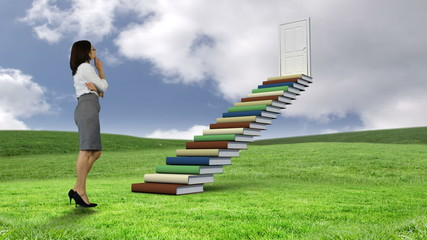 Businesswoman looking at stair made of books