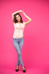 Happy young woman posing over pink background