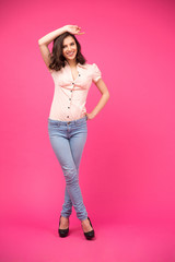 Smiling woman posing over pink background