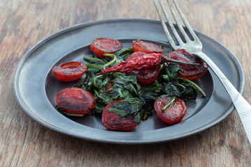 Fried tomatoes with spinach leaves and chili.