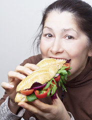 Woman with a sandwich with tomatoes, red onion and arugula.