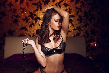 Sexy woman with handcuffs in bedroom