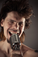 man with disheveled hair singing into retro microphone