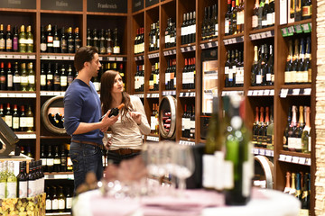 young couple buys a bottle of red wine in the store