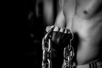 Close up Muscular Man holding Chains on Black Background