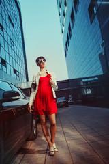 Beautiful young businesswoman is walking near skyscrapper.