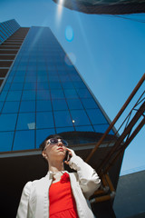 Beautiful young businesswoman is calling near skyscrapper.