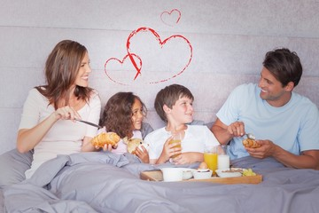 Composite image of family having breakfast in bed