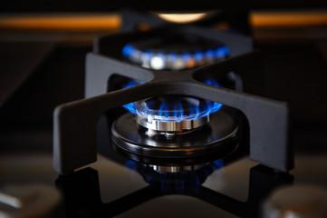 Lit gas burner on a glass plate closeup