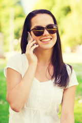 smiling young girl with smartphone outdoors