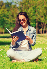smiling young girl with book sitting in park
