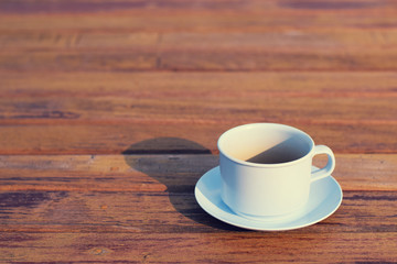 Coffee cup on wooden table (vintage background)