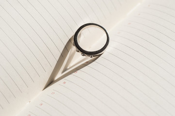 wedding ring is on the page diary and makes a shadow in the form
