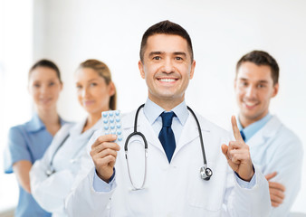 smiling male doctor in white coat with tablets