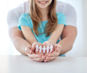 close up of man and girl with cupped hands at home