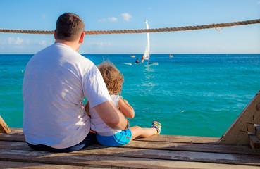 bambino e papà seduti sul molo