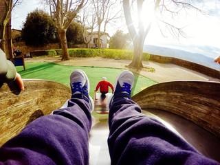 bambino gioca al parco sullo scivolo, punto di vista particolare