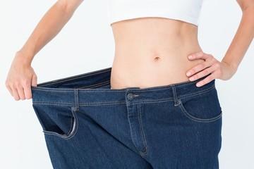 Slim woman wearing too big jeans