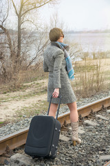 Young woman with a suitcase and a camera on the rails