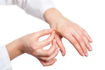 Hand putting adhesive bandage