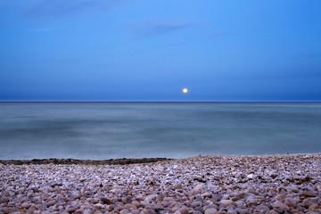 Luna sobre playa de piedras