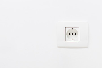 Empty white electric socket on a white wall