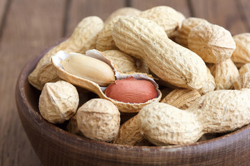 Rustic wood bowl of peanuts in shells. In perspective.