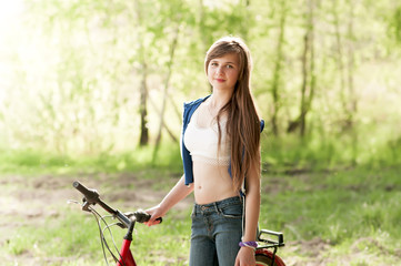 Portrait of pretty teenage girl with bicycle on green trees back