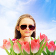 little girl in sunglasses and tulips on sky background