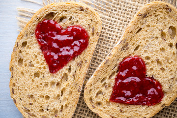 Grain slice of bread with jam heart shape.
