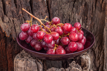 Red grapes in plate on log