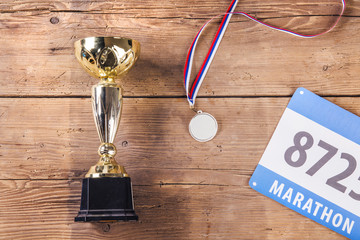 Cup, medal and race number laid on a wooden floor background