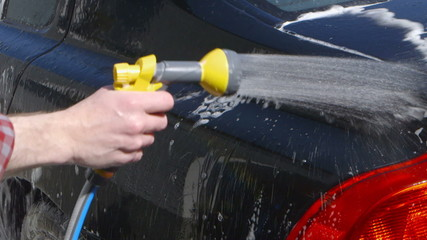 Car Care - Man using a garden spray gun to remove the soap