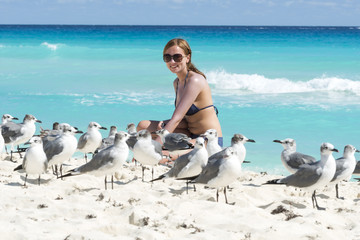 Young woman with seagulls on the beach in Cancun, Mexico.