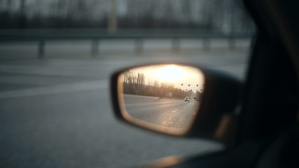 View of the road in the rearview mirror at sunset