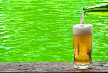 Beer with green water ripple on background.
