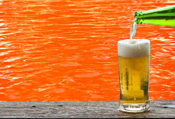 Beer with red water ripple on background.
