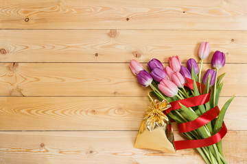 Tulips and gift on wooden texture