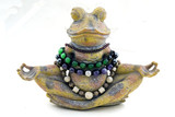 stone frog meditates on a white background