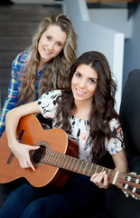 Two young girls playing guitar at home