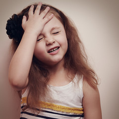 Upset kid girl thinking with hand on the head. Vintage color por