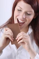 Frau beisst in eine Tafel Schokolade