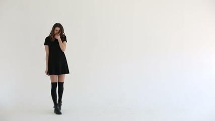 Woman flirts looking at camera white studio background
