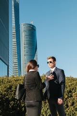 Business Couple Talking in the Street Besides a Financial Area