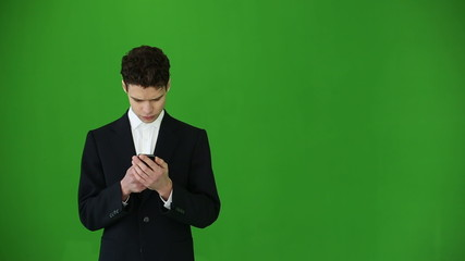 Young businessman using smartphone at chroma key background